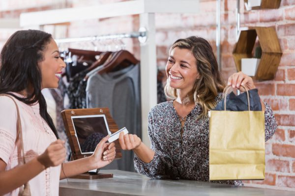 A mixed race African American woman shopping in a clothing store, paying by credit card at the checkout counter. The cashier is handing her the shopping bag.
